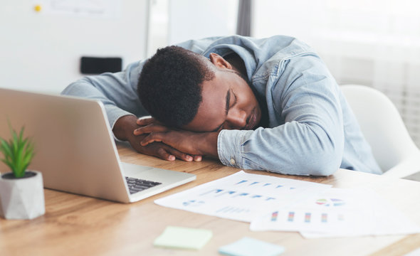 Overworked african american employee sleeping at workplace in office