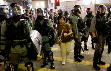 A woman makes her way between riot police as they disperse pro-democracy demonstrators gathering to commemorate the three-month anniversary of an assault by more than 100 men on protesters, commuters and journalists, in Hong Kong