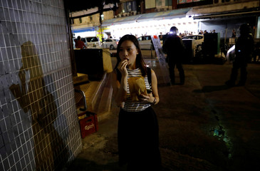 A woman eating a snack walks past riot police officers dispersing pro-democracy demonstrators gathering to commemorate the three-month anniversary of an assault by more than 100 men on protesters, commuters and journalists, in Hong Kong