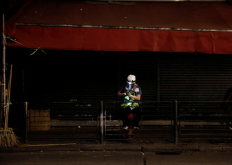 A journalist wearing a helmet and mask sits in the street while riot police prepare to disperse pro-democracy demonstrators gathering to commemorate the three-month anniversary of an assault by more than 100 men on protesters, commuters and journalists, in