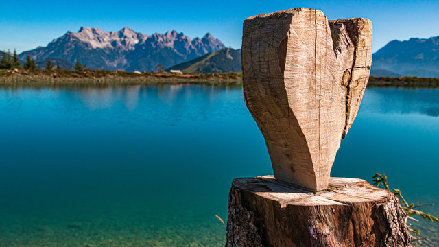 Beautiful alpine view with a heart carved from a tree stump and reflections in a lake at Fieberbrunn, Tyrol, Austria