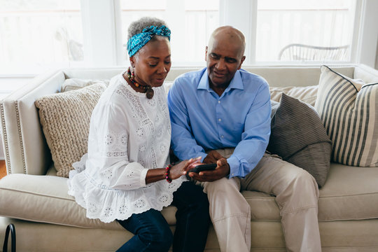 Senior couple looking at pictures on mobile phone