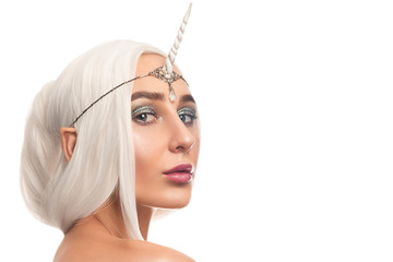 Beautiful woman unicorn closeup stylish makeup with glitter posing on isolated white background. Halloween look concept. Beautiful girl with unicorn horn. copy space