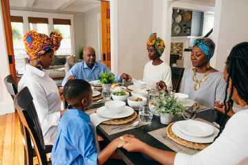 Family prays together at dinner table