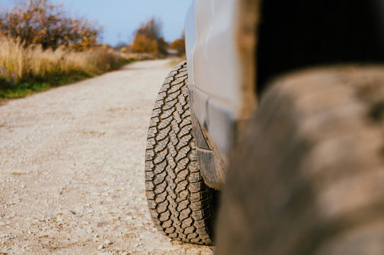 All terrain tires are covered with dirt close up on rocky road