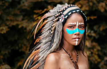 The abstract art design bakcogrund of  beautiful woman wearing headdress feathers of birds. American Indian girl in native costume,posing in forest,vintage and art tone,blurry light around