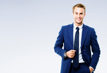 Portrait picture of happy smiling young businessman, over grey background. Business success concept.