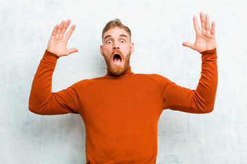 young red head man wearing turtle neck screaming with hands up in the air, feeling furious, frustrated, stressed and upset against cement wall