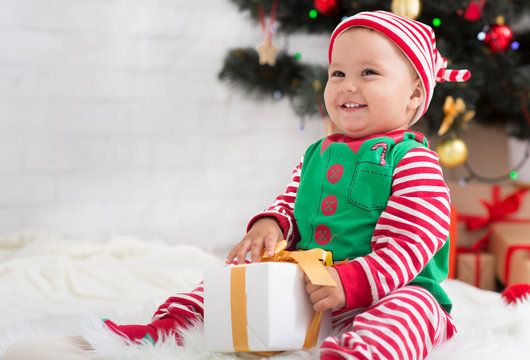 Adorable toddler enjoying Christmas time, playing with gift box