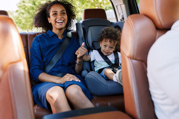 Happy mother and her son sitting on a backseat while traveling in a car