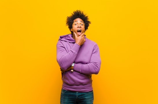 young black man with mouth and eyes wide open and hand on chin, feeling unpleasantly shocked, saying what or wow against orange wall