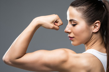 Portrait of a beautiful fitness woman showing her biceps isolated on gray background