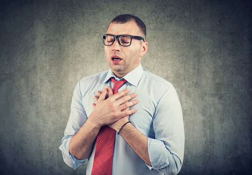Young man having asthma attack or chest pain