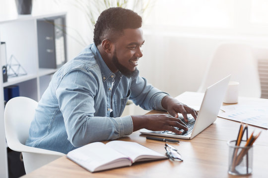 Portrait of smiling employee working on laptop in office