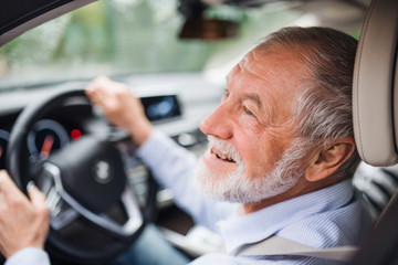 Close-up of happy senior man sitting in car in driver seat, driving.