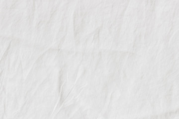 White crinkle linen texture. Closeup of fabric, tablecloth or bed linen. Light empty copy space.