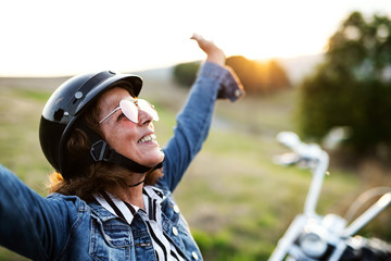A cheerful senior woman traveller with motorbike in countryside.