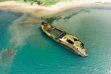 Canvas Prints Ship Shipwreck of old wooden ship in turquoise water of sea on coast, aerial view. Vityaz Bay, Primorsky Krai, Far East, Russia