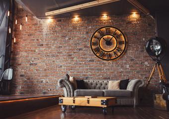 Loft style sitting-room brick and clocks