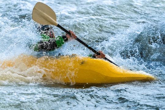 Man in a yellow kayak white water rafting