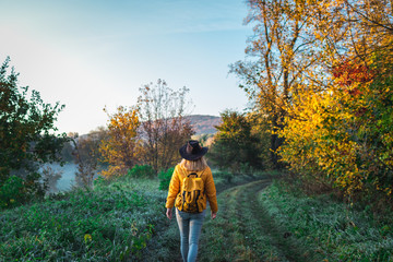 Hiker walking on dirt road in countryside at autumn. Woman hiking at cold morning