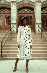 Woman standing with polka dot dress and hat in front of building
