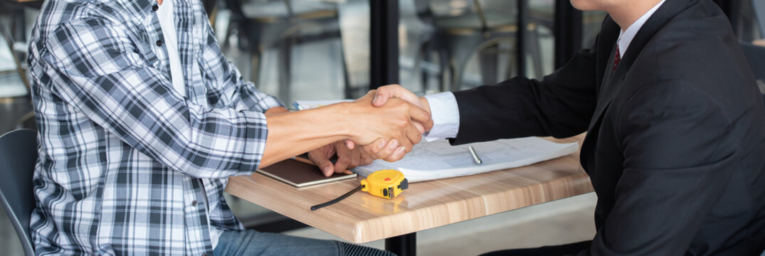 Professional businessman shaking hands with builder on construction site, handshake concept.