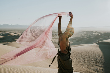 Side view of man holding net in desert