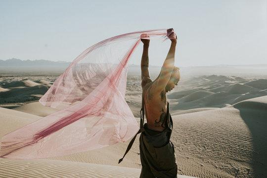 Side view of man holding net in desert