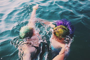 Overhead view of two people with colored hair underwater