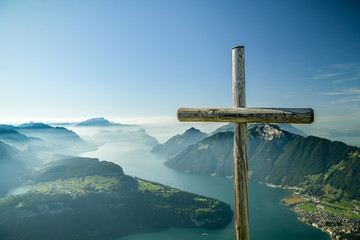 Wall Mural - Wooden cross on viewing platform on top of Fronalpstock peak above the small village of Stoos