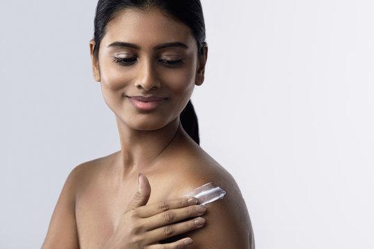 Beautiful Indian woman applying moisturizing cream or sunblock lotion on her body