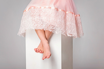 Little cute girl in pink dress is sitting barefeet on white cube. Cropped.