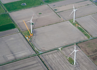 Aerial view of wind turbine or windmill construction with crane on field, Nordfriesland, Germany.