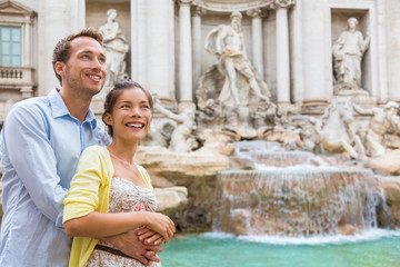 Wall Mural - Rome travel tourists couple at Trevi Fountain in Rome, Italy vacation. Happy young romantic interracial couple traveling in Europe. Man and Asian woman embracing together.