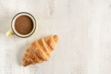 Crispy croissant and cup of coffee on a wooden table