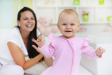 Smiling mom and baby lying in bed, baby in front , looking at camera.Shallow doff