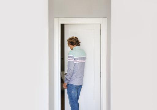 Man opening the door of him home.