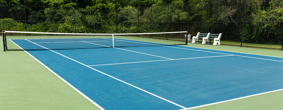 Sie view of blue tennis court with green boarder and benches to rest on
