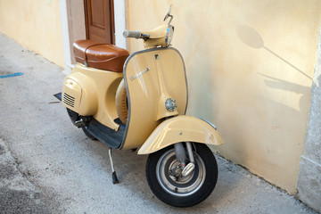Classic yellow Vespa scooter stands in a town