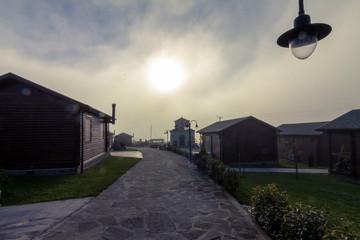 Bungalow-Siedlung mit kleiner Kapelle im Morgennebel