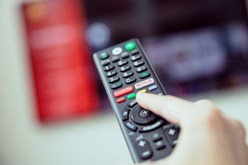WROCLAW, POLAND - APRIL 03rd, 2018: Woman's hand is holding a TV remote control with streaming media services. Streaming media is multimedia that is constantly received and presented to an end-user