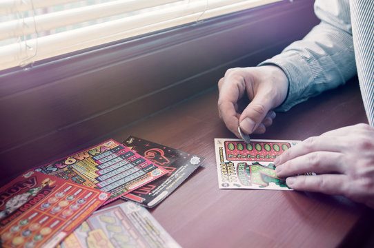 WROCLAW, POLAND -  MARCH 28th, 2017: Man scratches Polish lottery scratchcard. Scratchcard is a small card, where areas contain concealed information which can be revealed by scratching off