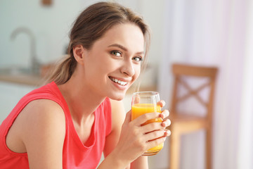 Foto op Canvas Sap Young woman drinking healthy juice in kitchen. Diet concept