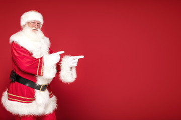 Real Santa Claus pointing on red studio background.