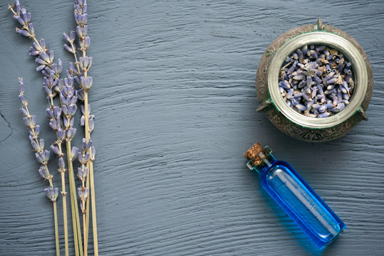 Blue lavender essential oil bottle and dried lavender flowers on gray wooden table background.