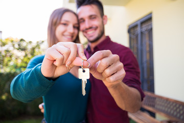 Couple in love holding up new house key