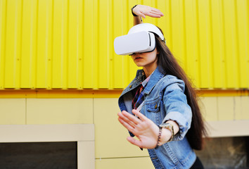 young woman in virtual reality glasses in denim jacket on yellow wall background