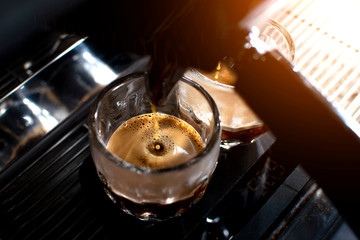 coffee machine makes double espresso in glasses, close-up of coffee preparation, drops fall in a cup