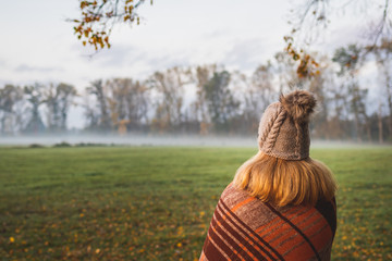 Woman with blanket and knit hat enjoying cold misty morning outdoors